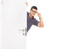 Man with glasses peeking behind a door. Isolated on white background Stock Images