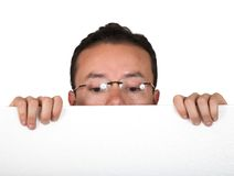 Man with glasses peeping over white card Stock Image