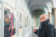 Man in glasses with the phone in gallery of pictures in winter Stock Photo