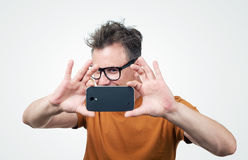 Man in glasses photographed by smartphone Royalty Free Stock Images