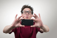 Man in glasses photographed by smartphone Stock Images