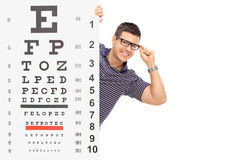Man with glasses posing behind an eyesight test Stock Images