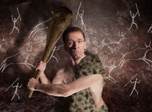 A man in glasses and in primitive skin with a cudgel in his hands threatens royalty free stock images