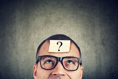 Man in glasses with question mark looking up. Thinking man in glasses with question mark looking up on gray wall background royalty free stock photos