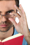 Man in glasses reading Royalty Free Stock Images