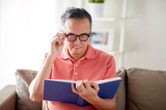 Man in glasses reading book at home. Vision, leisure, literature and people concept - man in glasses sitting on sofa and reading book at home Stock Photos