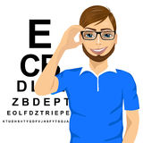 Man with glasses reading sight test characters Stock Photo