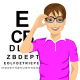 Man with glasses reading sight test characters Royalty Free Stock Photos