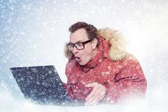 Man in glasses and red winter clothes with laptop, cold, snow. Man in glasses and red winter clothes with laptop, cold, snow royalty free stock photos