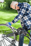 Man in glasses repaired pedals a bicycle Royalty Free Stock Photography