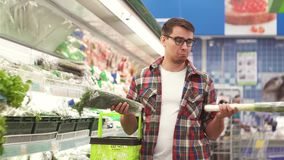 A man with a basket is faced with a choice of what to buy in the Department with vegetables in the supermarket. A man with glasses and a shirt with a basket is stock video