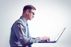 Man in glasses, shirt and tie is working on laptop, side view. Royalty Free Stock Photos
