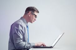Man in glasses, shirt and tie is working on laptop, side view. Stock Photos
