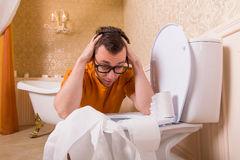 Man in glasses sits resting his hands on toilet Stock Photography