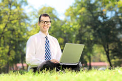 Man with glasses sitting on a grass and working on a laptop Stock Photos