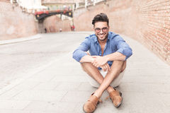 Man with glasses sitting on the sidewalk in a city Royalty Free Stock Images