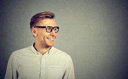 Man with glasses smiling looking to the side. Young man with glasses smiling looking to the side Stock Photo