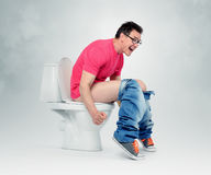 Man with glasses straining on the toilet. Royalty Free Stock Image