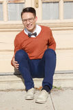 Man with glasses and sweater sitting on steps in front of house Stock Images