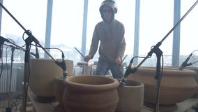 A drummer man plays a quick tune on clay pots. A man in glasses and a sweatshirt plays a rhythmic melody on clay pots stock video