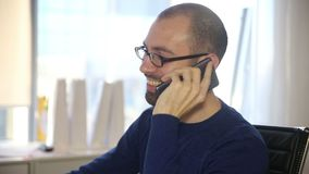 The man in glasses talking phone and laughs.  stock footage