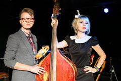 Man in glasses with tambourine and woman with contrabass Royalty Free Stock Photo