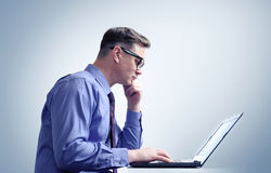 Man with glasses thinking in front of a laptop Royalty Free Stock Photography