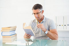 Man with glasses thinking and reading a book Royalty Free Stock Images