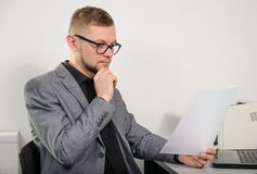 A man in glasses thoughtfully studying the documents. A man in glasses and a jacket thoughtfully studying the documents for work at the table with a laptop and a Stock Photo