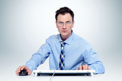 Man with glasses and tie at the keyboard in front of computer Stock Photography