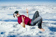 The man in glasses virtual reality flying on sky Stock Photo