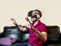 The man in glasses virtual reality plays  on the  sofa Stock Image