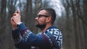 Man in glasses is walking through the autumn forest and makes photo by smartphone. Slow motion stock video footage