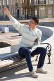 Man with glasses in white sweater siting on bench and holding ne Royalty Free Stock Images
