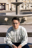 Man with glasses in white sweater siting on bench next to founta Stock Photo