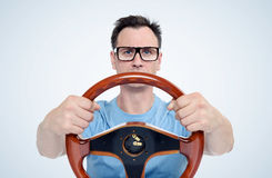 Man in glasses with wooden steering wheel, car driver concept. On blue background Stock Image