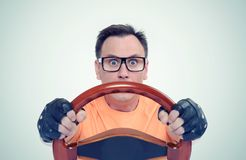 Man in glasses with wooden steering wheel, car driver concept Stock Photos