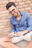 Man with glasses working on his tablet and smiles Royalty Free Stock Photography