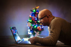 Man with glasses working on a laptop near the Christmas tree Stock Photography