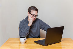 A man with glasses is working on a laptop Royalty Free Stock Image