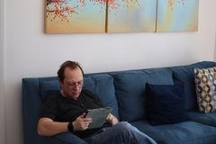 A man with glasses is working on a tablet. man relaxing in room sitting on the couch. Interested attractive man sitting on a sofa stock photography