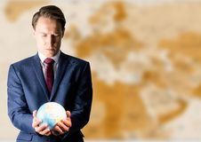 Man with globe against brown blurry map Stock Images