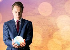 Man with globe against map with bokeh Stock Photo