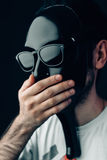 Man in glossy black mask and sunglasses closes mouth by hand. Vertical studio portrait in close-up. Royalty Free Stock Photography