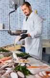 Man in glove behind counter shows fish in his hand Stock Photography