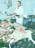 Man in glove behind counter shows fish in his hand Royalty Free Stock Photo