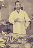 Man in glove behind counter shows fish in his hand Royalty Free Stock Image