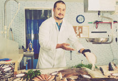 Man in glove behind counter shows fish in his hand Stock Image