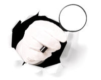 Man with gloves is holding magnifying glass in his finger through a hole. Man with gloves is holding magnifying glass through a hole in white paper Stock Image