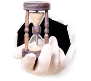 Man with gloves is holding sand clock in his finger through a hole. Man with gloves is holding sand clock through a hole in white paper Royalty Free Stock Photo